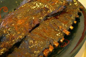 A plate of ribs in flattering yellow light.