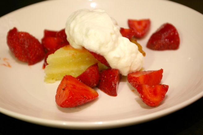 Lemon slice topped with peppered strawberries and whipped cream with honey.